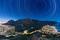 Stars trail above and urban lights sprawl below in