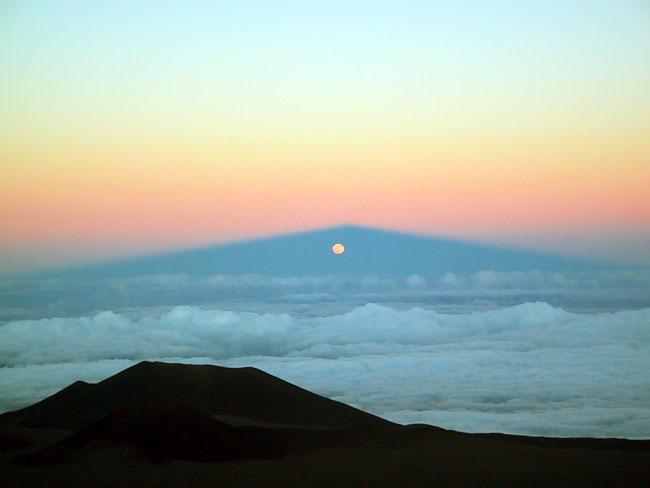 La luna sale a través de la sombra del Mauna Kea