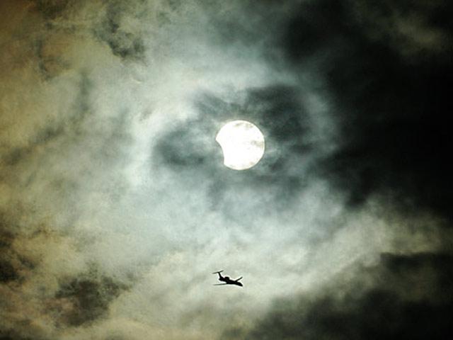 Nubes, avión, Sol y eclipse