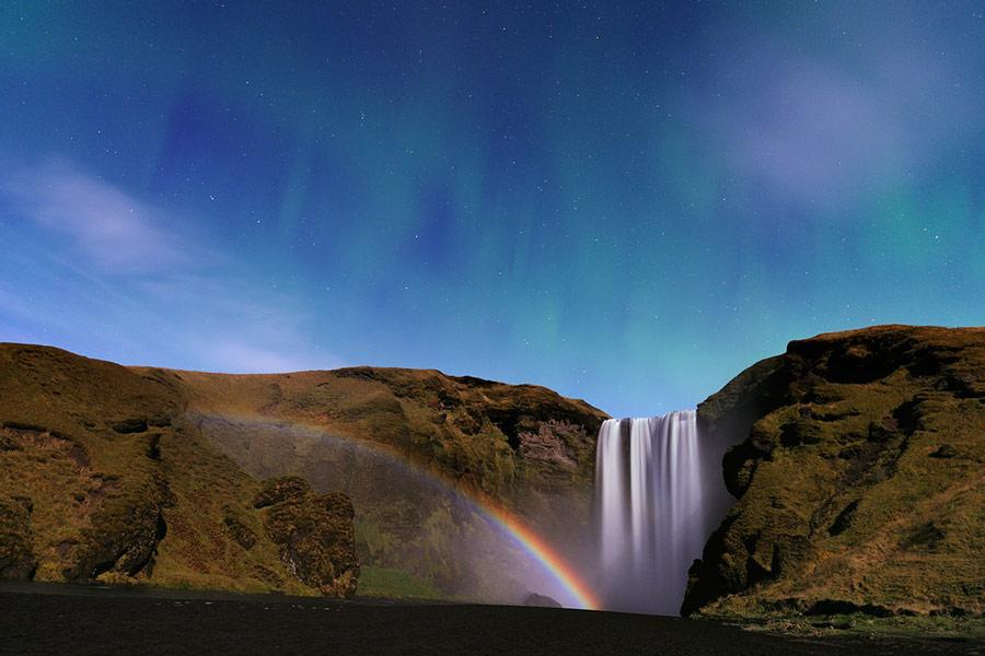 Cascada, arco de Luna y aurora en Islandia