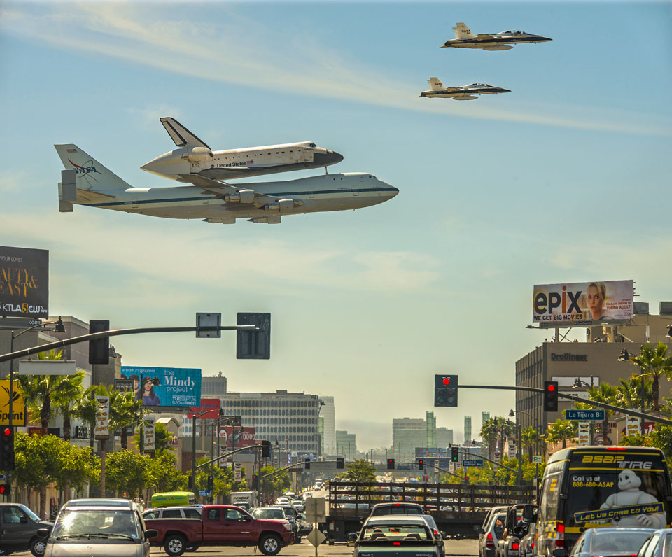 A shuttle riding on a jet plane, escorted by fighters, flies low over a Los Angeles street