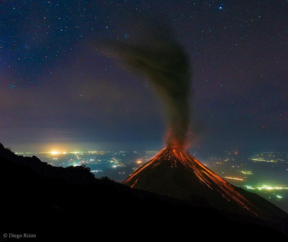 Volcán de fuego en erupción bajo las estrellas