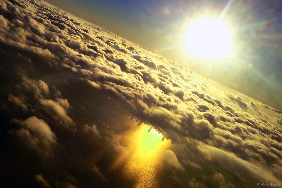 Ciudad invertida por debajo de las nubes