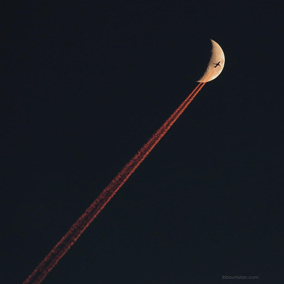 Avión que cruza una luna creciente