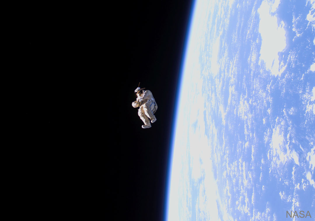 A spacesuit is shown floating high above the Earth. See Explanation.