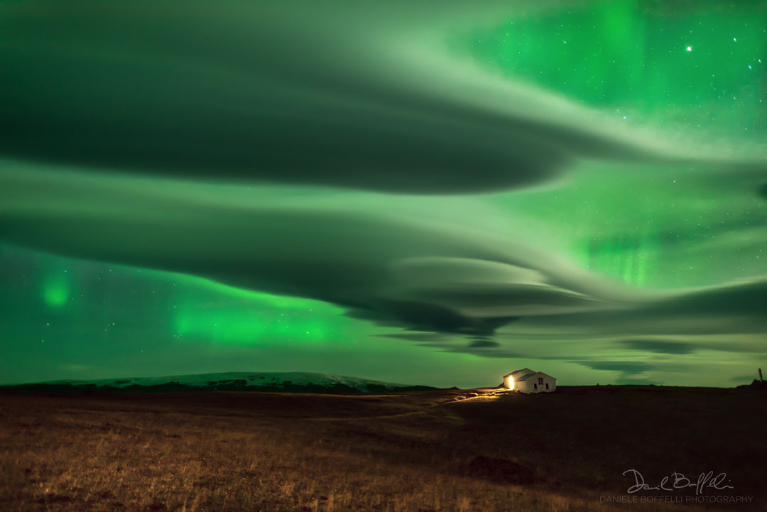 The picture shows green aurora through odd lenticular clouds. Please see the explanation for more detailed information.