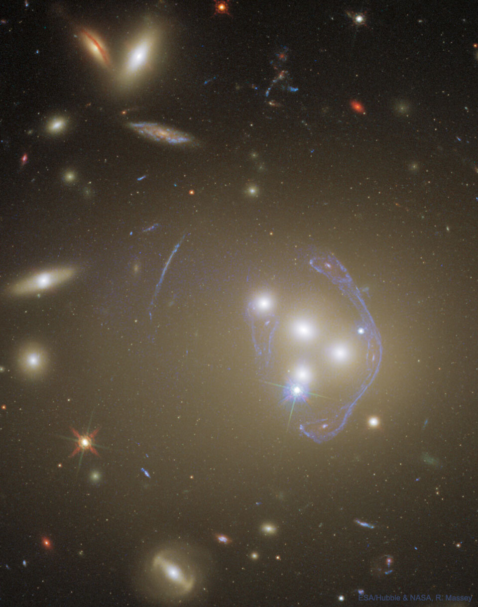 The picture shows galaxy cluster Abell 3827 from Hubble. Cluster galaxies are seen merging and a complex image of a background galaxy  is seen where the cluster acts as a gravitational lens.  Please see the explanation for more detailed information.