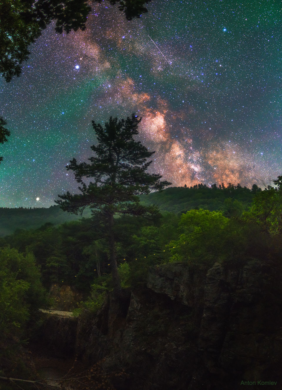 The picture shows an arching Milky Way Galaxy with a firefly  path in the foreground over Russia. Please see the explanation for more detailed information.