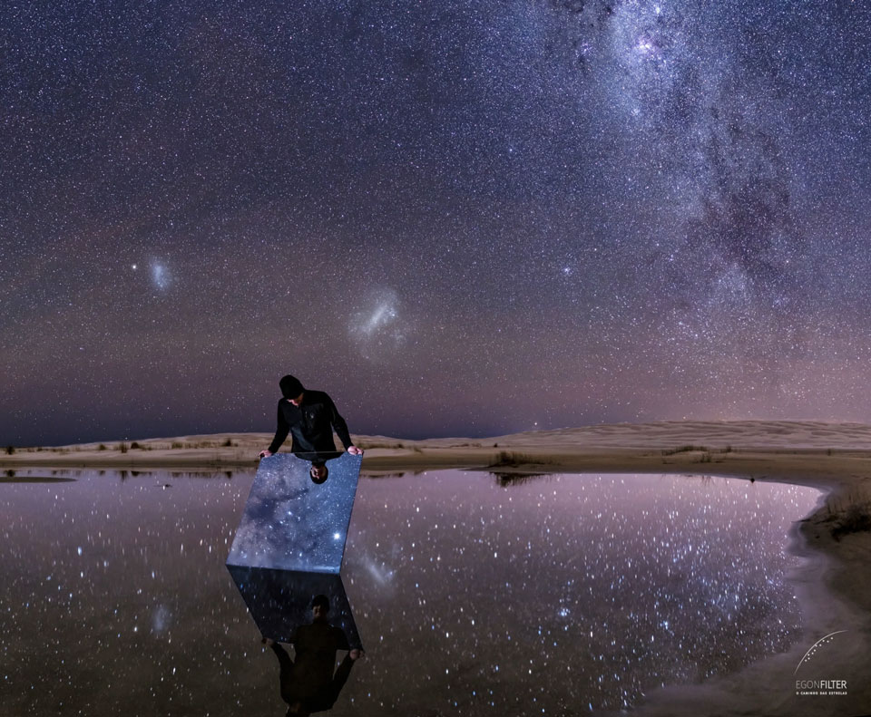 The picture shows a clear night sky from Brazil that is not only reflected from standing water but by a person holding a mirror. Please see the explanation for more detailed information.
