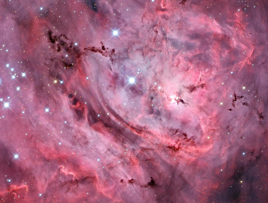 The Deep Lagoon -  Ridges of glowing interstellar gas and dark dust clouds